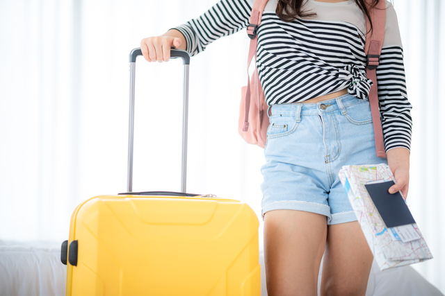 a young asian women travel with yellow suitcase