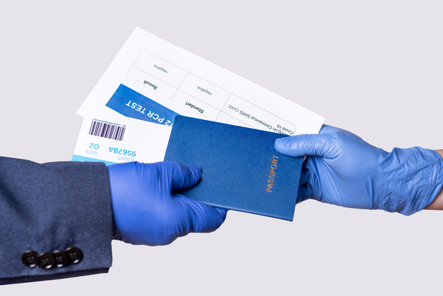 Gloved hands holding out documents for air travel to the officer to check.